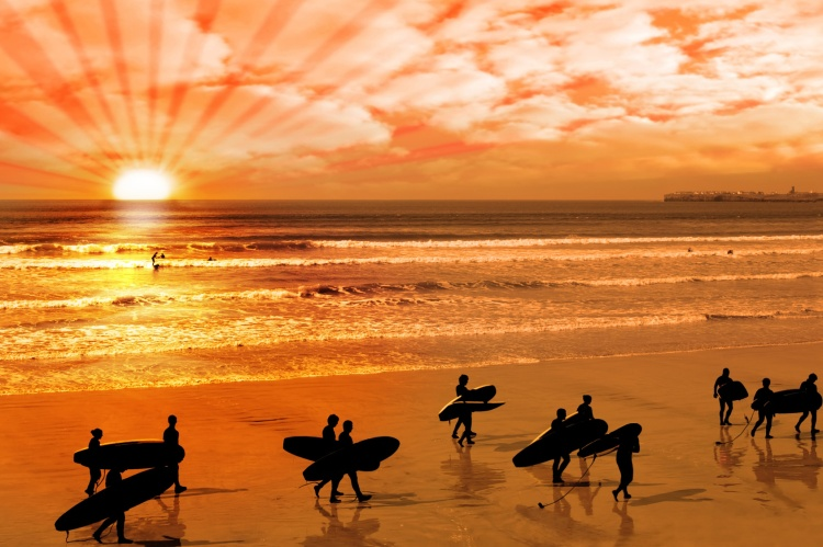 surfers walking on glorious sunset beach